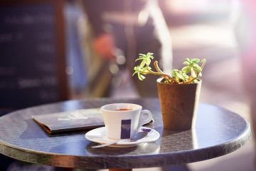 morning-coffee-on-outside-cafe-table-with-plant-menu